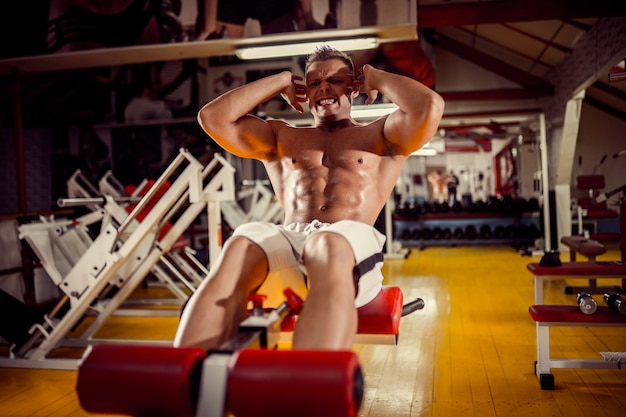 Jeune homme faisant des exercices abdominaux assis bench press in gym