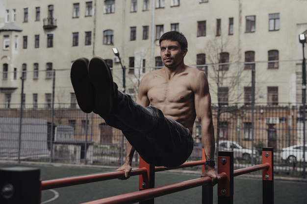 Jeune homme faisant des exercices abdominaux à barres parallèles.