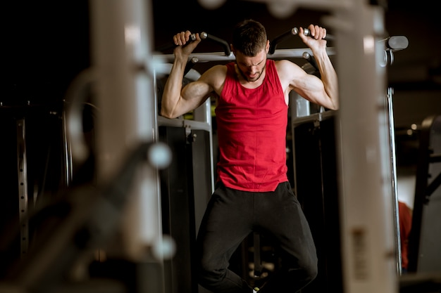 Jeune homme faisant des exercices pour le dos avec machine d'exercice dans un club de gym