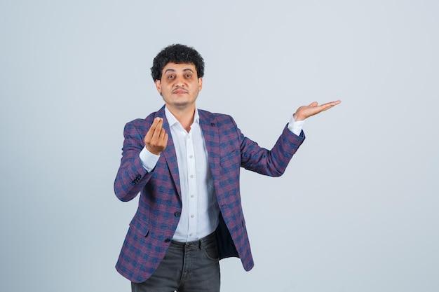 Jeune homme faisant un geste d'argent, prétendant tenir quelque chose en chemise, veste, pantalon et ayant l'air plein d'espoir. vue de face.