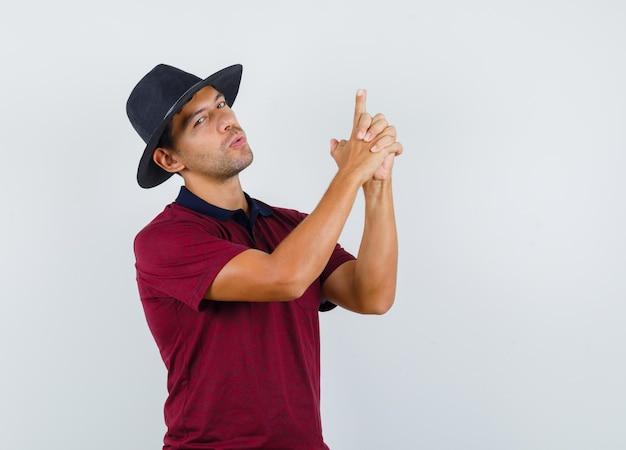Jeune homme faisant un geste d'arme à feu en t-shirt, chapeau et l'air confiant. vue de face.