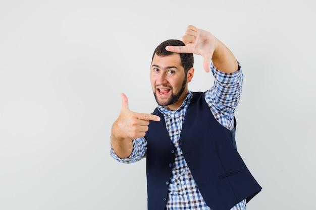 Jeune homme faisant le geste du cadre en chemise, gilet et à la fringante, vue de face.