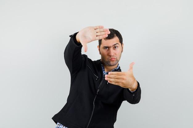 Jeune homme faisant le geste du cadre en chemise, veste et à la prudence