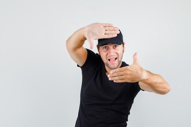 Jeune homme faisant le geste du cadre en t-shirt noir, casquette et à la joyeuse