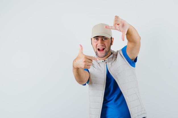Jeune homme faisant le geste du cadre en t-shirt, veste et à la joyeuse, vue de face.