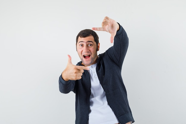 Jeune homme faisant le geste du cadre en t-shirt, veste et à la recherche de plaisir. vue de face.