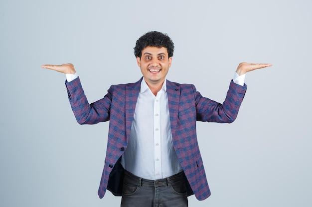 Jeune homme faisant un geste d'écailles en chemise, veste, pantalon et l'air confiant, vue de face.