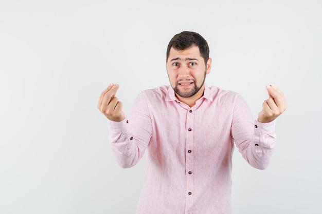 Jeune homme faisant un geste italien en chemise rose
