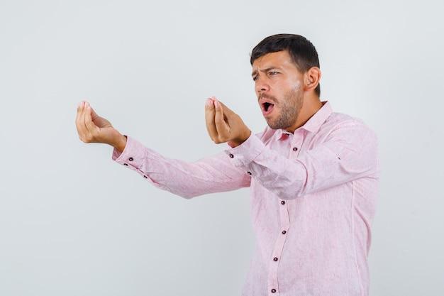 Jeune homme faisant un geste italien et criant en vue de face de chemise rose.