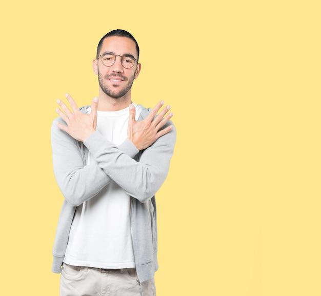 Jeune homme faisant un geste numéro dix