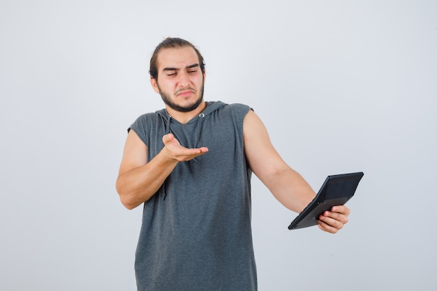 Jeune homme faisant un geste de question en sweat à capuche et à la vue de face, mécontent.