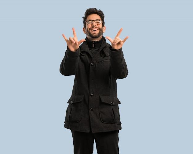 Jeune homme faisant un geste rock