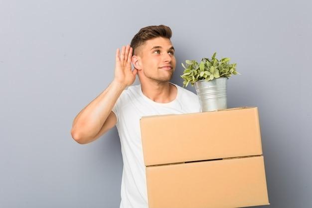 Jeune homme faisant un geste tenant des boîtes essayant d'écouter un potin.