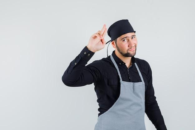 Jeune homme faisant des gestes avec deux doigts en l'air en chemise, tablier et à la cool, vue de face.