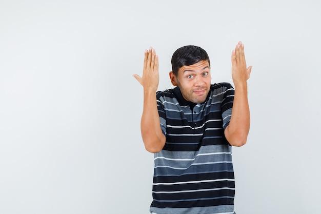 Jeune homme faisant des gestes avec les mains levées en t-shirt et à la joyeuse vue de face.
