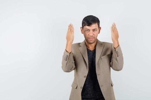 Jeune homme faisant des gestes avec les mains levées en t-shirt, veste et à la joyeuse vue de face.