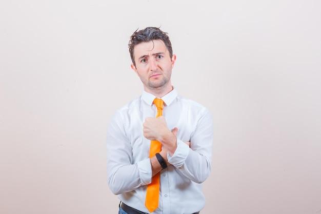 Jeune homme faisant des gestes pour demander en chemise blanche et ayant l'air confus