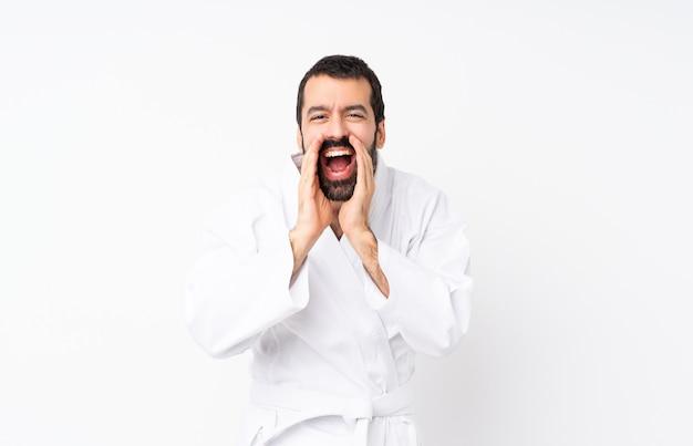 Jeune homme faisant karaté sur fond blanc isolé criant et annonçant quelque chose