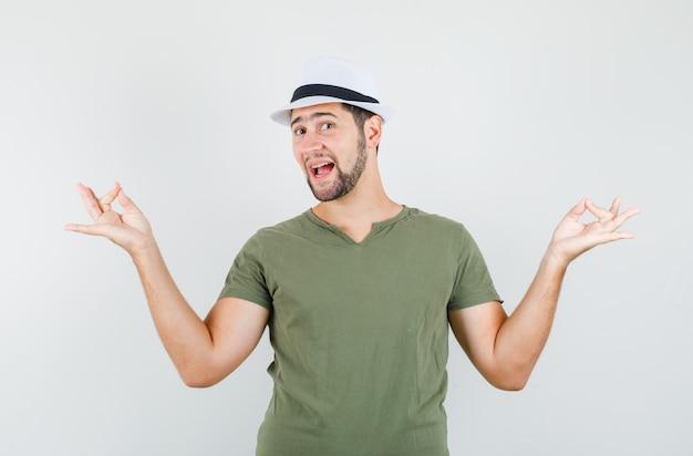 Jeune homme faisant la méditation en t-shirt vert et chapeau et à la bonne humeur