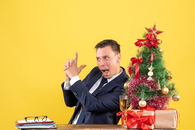 Jeune homme faisant un pistolet à doigt assis à la table près de l'arbre de noël et présente sur jaune