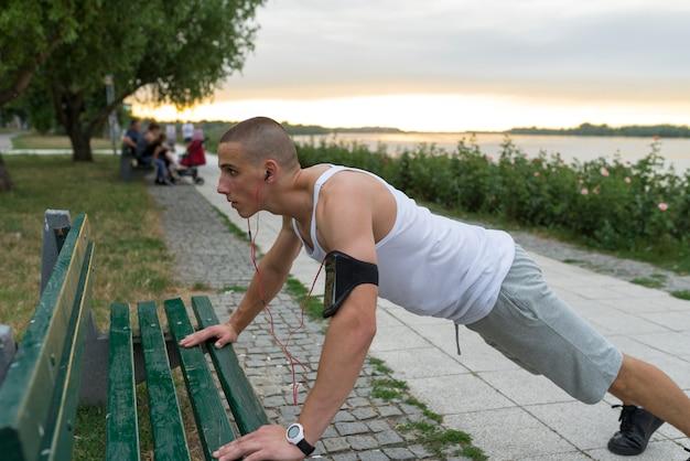 Jeune homme faisant des pompes en plein air
