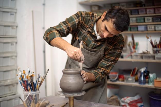 Jeune homme faisant de la poterie en atelier