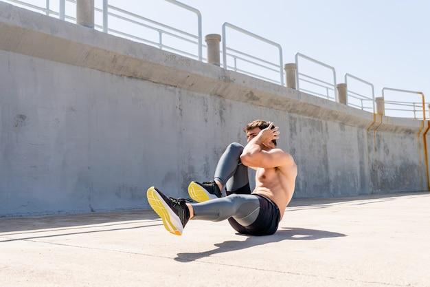 Jeune homme faisant des redressements assis sans chemise dans la rue à midi