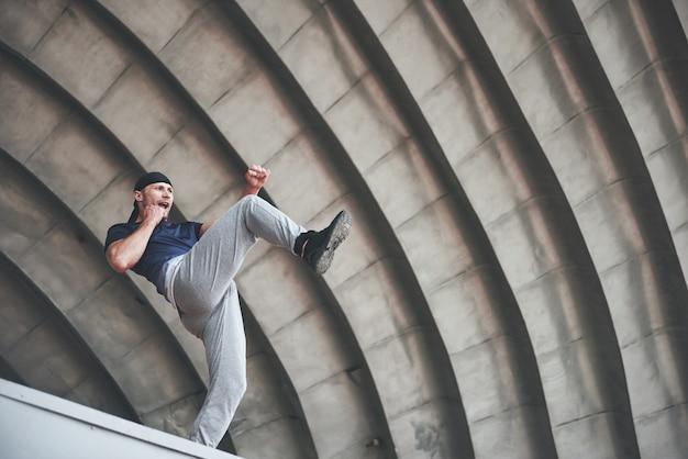 Jeune homme faisant un saut parkour dans l'espace urbain dans la ville ensoleillée printemps été.