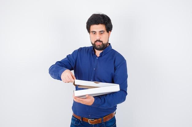 Jeune homme faisant semblant d'ouvrir une boîte à pizza en chemise, jeans et l'air étonné, vue de face.
