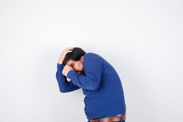 Jeune homme faisant semblant de se défendre en chemise, jeans et l'air offensé. vue de face.