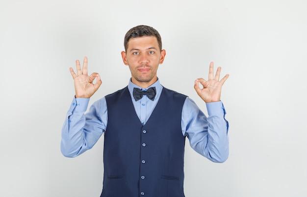 Jeune homme faisant signe ok et souriant en costume