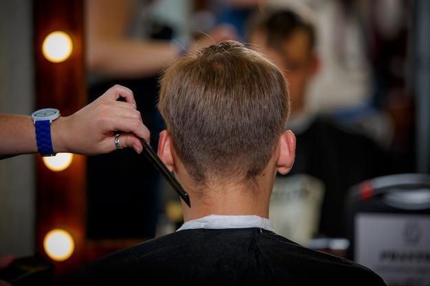 Un jeune homme fait une coupe de cheveux dans le salon.