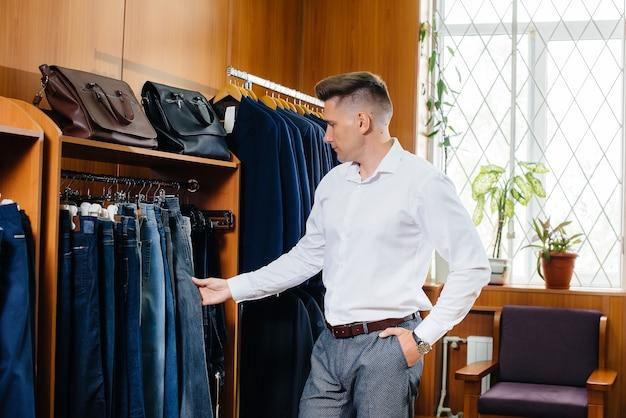 Un jeune homme fait des courses et prend un costume d'homme.