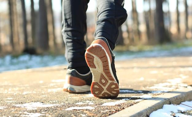 Le jeune homme fait du jogging dans le parc d'hiver