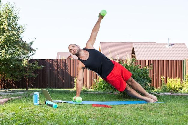 Le jeune homme fait du sport dans un parc. un sportif aux cheveux blonds fait une planche avec des haltères, regarde un film et étudie à partir d'un ordinateur portable sur un tapis dans l'arrière-cour en été
