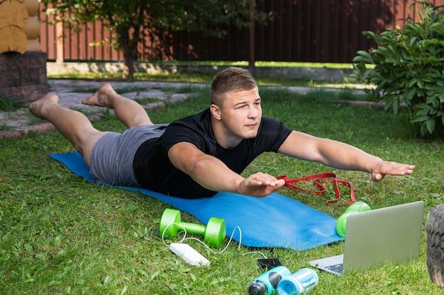 Le jeune homme fait du sport dans un parc. un sportif aux cheveux blonds fait une planche, regarde un film et étudie depuis un ordinateur portable sur un tapis dans l'arrière-cour en été