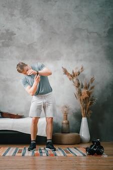 Le jeune homme fait du sport à la maison. enthousiaste sportif aux cheveux blonds met une montre de sport, se prépare à s'entraîner dans le b edroom