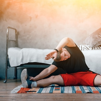 Un jeune homme fait du sport à la maison, entraînement en ligne. l'athlète s'étire, médite, assis sur une ficelle dans la chambre, à l'arrière-plan il y a un lit, un tapis.