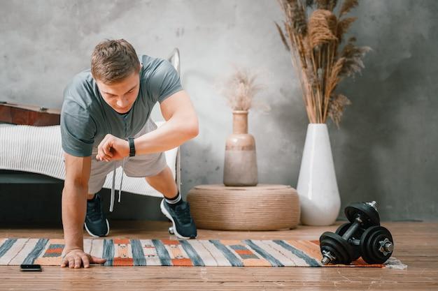 Un jeune homme fait du sport à la maison, s'entraîne en ligne. l'athlète fait une planche, regarde l'heure sur une montre de sport, un chronomètre dans la chambre, en arrière-plan un lit, un vase, un tapis.