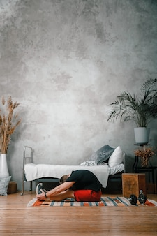 Un jeune homme fait du sport à la maison, une séance d'entraînement en ligne depuis le téléphone. l'athlète s'étire dans la chambre, en arrière-plan il y a un lit, un vase, un tapis.