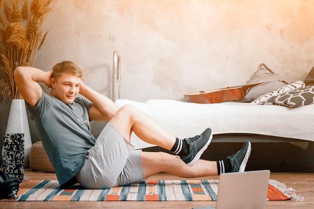Le jeune homme fait du sport à la maison. un sportif gai aux cheveux blonds fait la presse dans la chambre, à côté il y a un ordinateur portable avec une formation en ligne