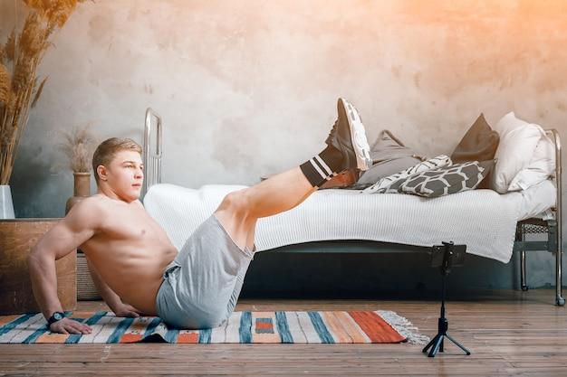 Le jeune homme fait du sport à la maison. un sportif gai aux cheveux blonds fait pression, levant les jambes, tirant un blog dans la chambre, à côté il y a un téléphone avec une formation en ligne