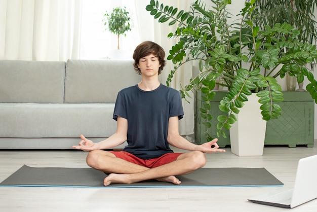 Un jeune homme fait du yoga à la maison. copiez l'espace. place pour le texte