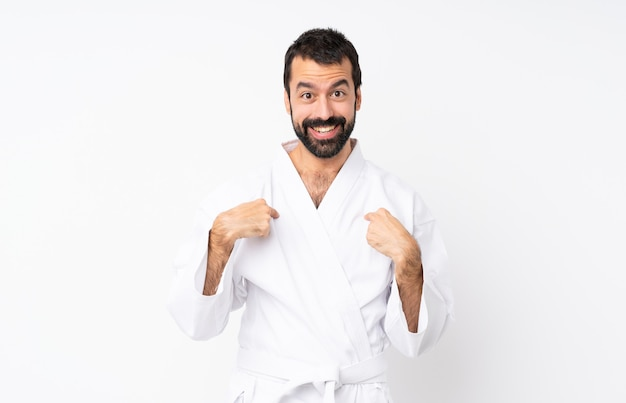 Jeune homme fait karaté sur blanc isolé avec une expression faciale surprise