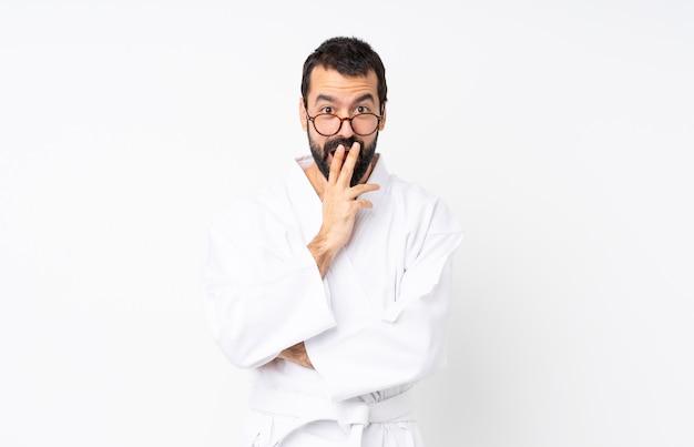 Jeune homme fait karaté sur blanc isolé avec des lunettes et surpris