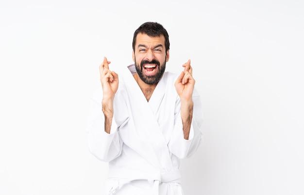 Jeune homme fait karaté sur fond blanc isolé avec les doigts qui se croisent