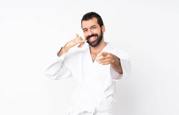 Jeune homme fait karaté sur fond blanc isolé, faisant un geste de téléphone et pointant devant
