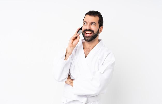 Jeune homme fait karaté sur fond blanc isolé, gardant une conversation avec le téléphone mobile
