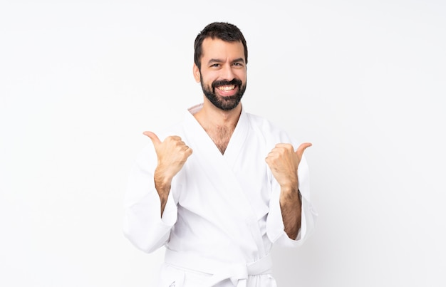 Jeune homme fait karaté sur fond blanc isolé avec les pouces vers le haut de geste et souriant