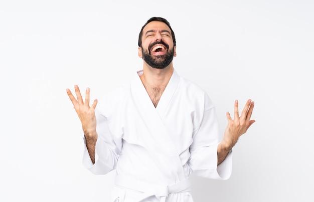Jeune homme fait karaté sur fond blanc isolé souriant beaucoup